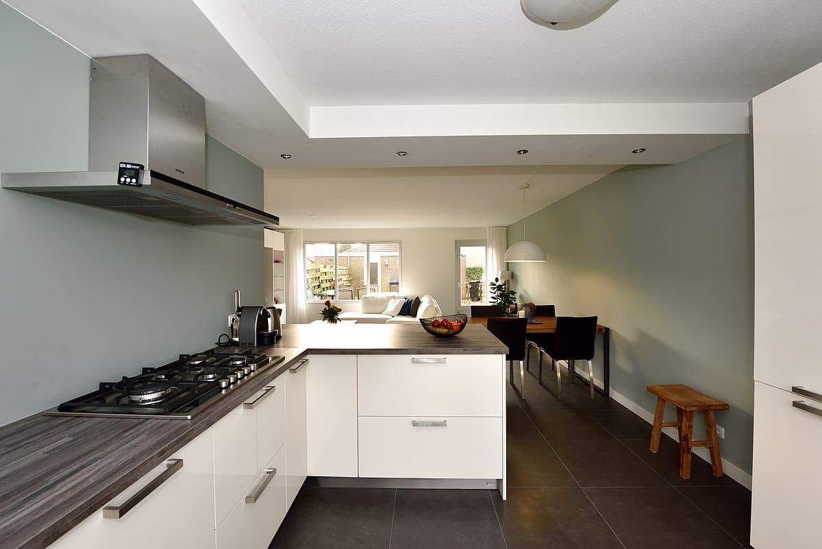 Strakke open keuken met groene muren