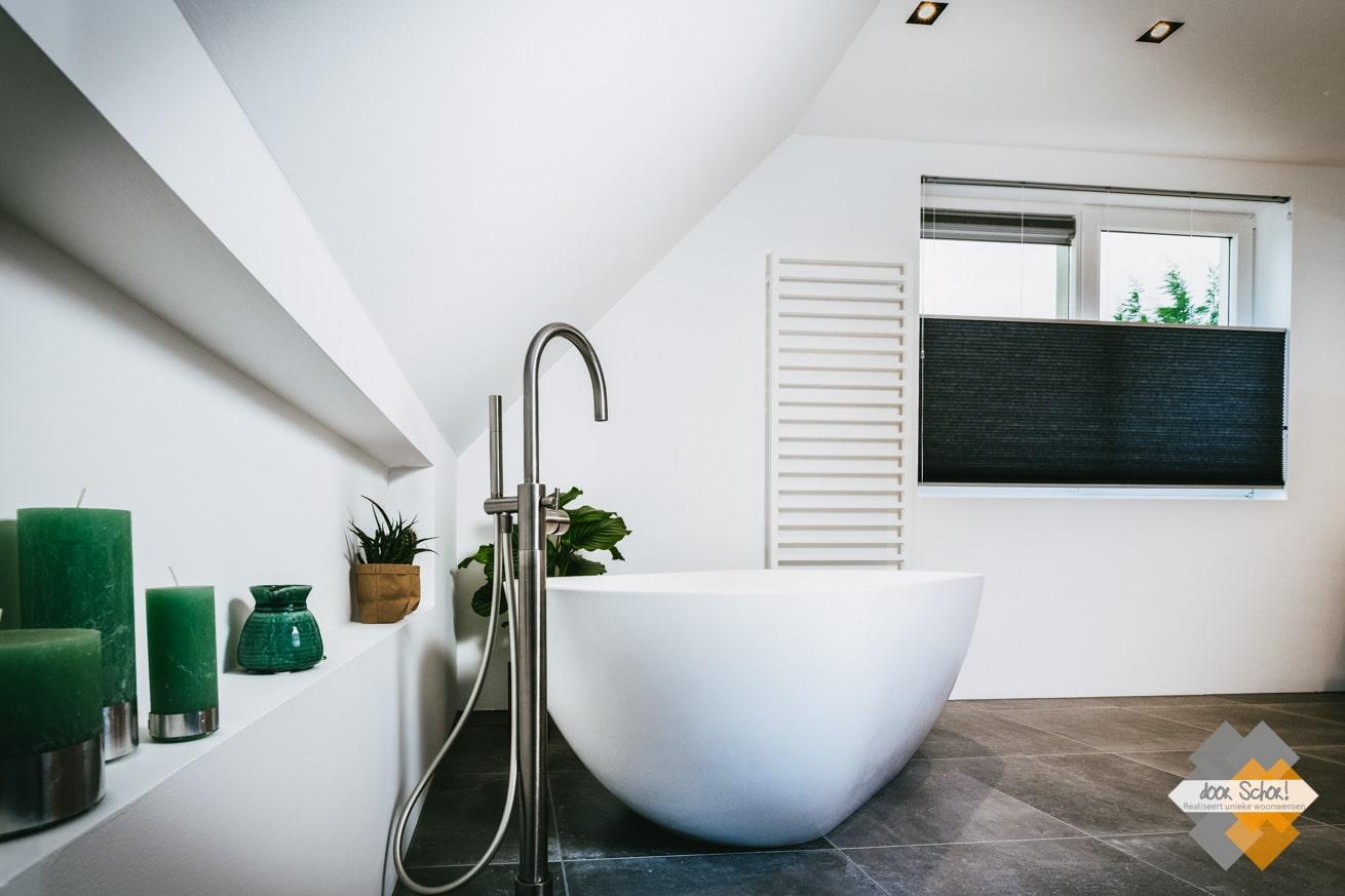 Vrijstaande RVS kraan naast een wit vrijstaand bad onder een schuin dak