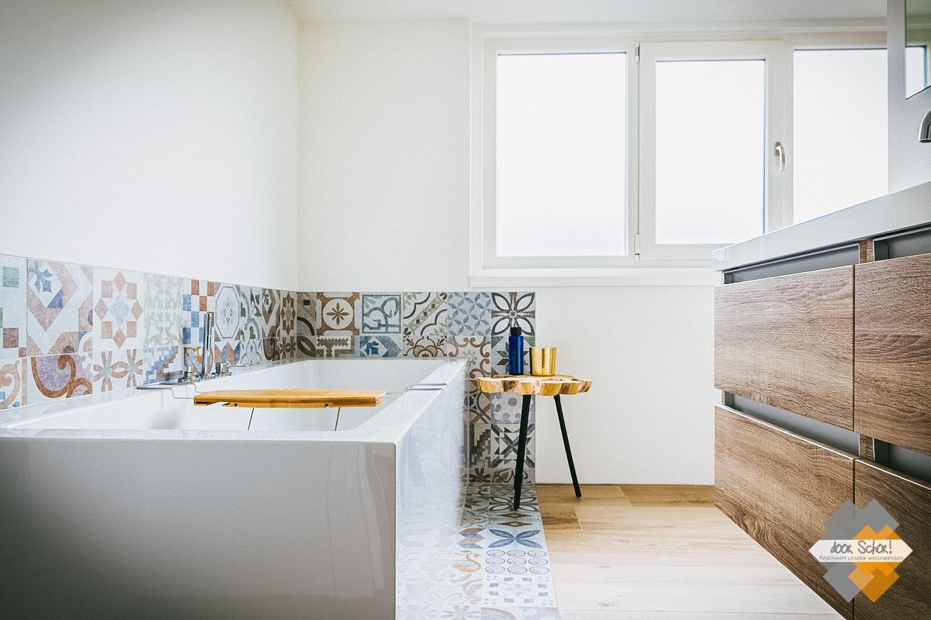 Deze badkamer is voorzien van een rechthoekig bad met strakke lijnen rondom voorzien van patroontegels