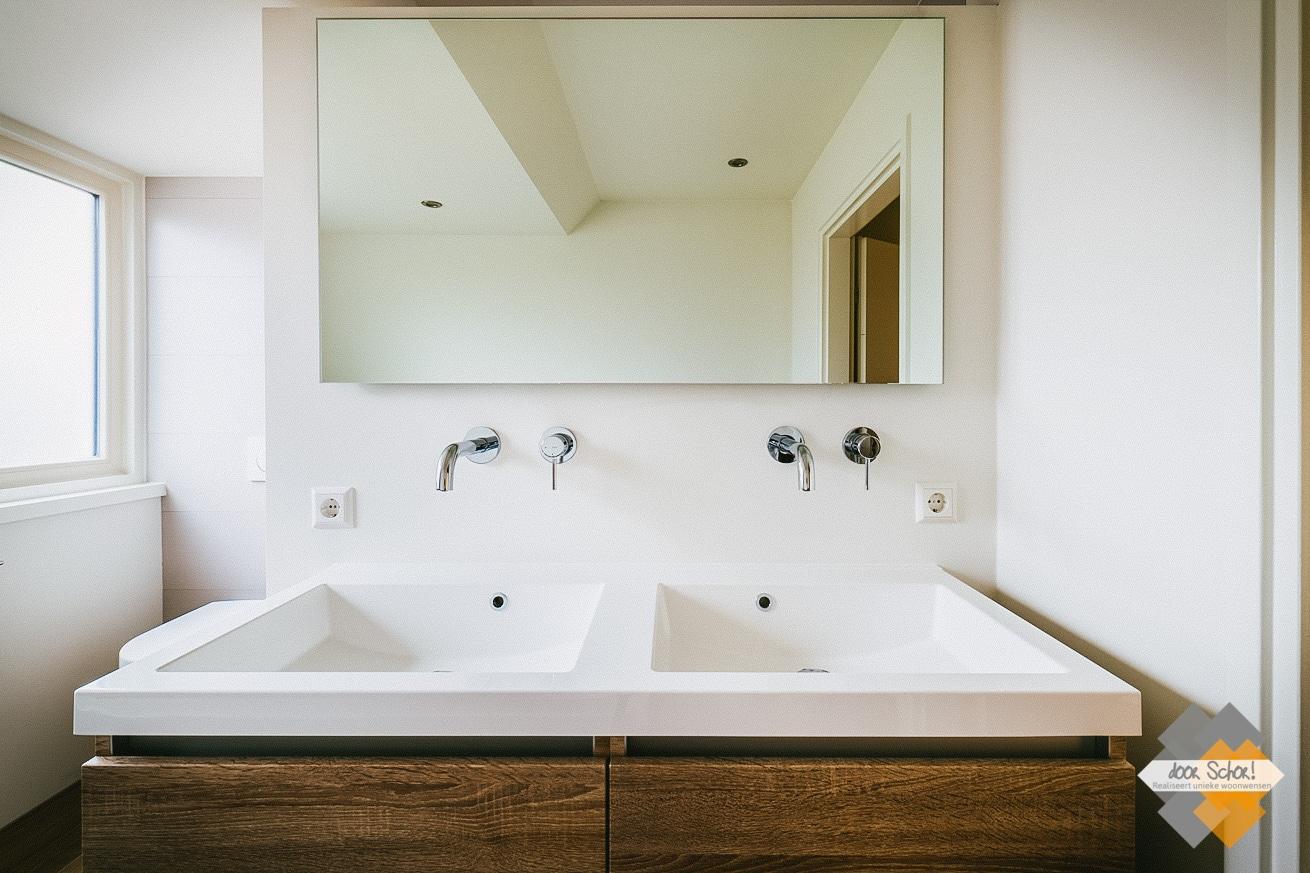 Eikenhouten badkamermeubel met een dubbele wasbak gecombineerd met twee vrij hangende kranen.